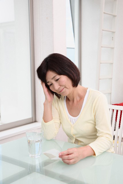 頭痛薬を飲む女性