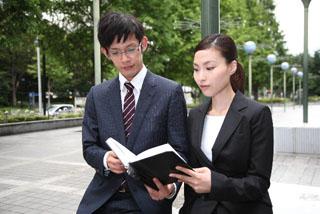 手帳をみるビジネスマンとビジネスウーマン